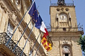 City hall with tower and various flags at Aix-en-Provence, France