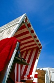 Low angle view of red and white striped beach chair