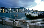 View of skyscrapers and moored ship at harbour with man in foreground, Hong Kong, China