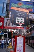 Die belebte Nathan Road in Kowloon mit Reklametafeln im Vordergrund
