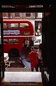 Red double-decker bus and porter standing with umbrella