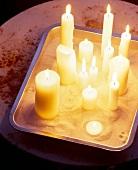 Flackernde Kerzen auf einem Backofen Bräter, mit Vogelsand ausgestreut