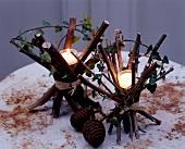 Bündel von Ästen, mit Bast gebunden, als rustikale Kerzenhalter