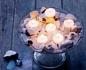 Teelichter auf Glas-Etagere, gefüllt mit Sand, Steinen und Glasscherben