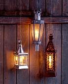 Drei Stall-Laternen mit flackernden Kerzen hängen an Drähten vor Wand