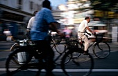 Men riding bicycle on street in Shanghai, China, blurred