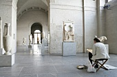 Woman sitting in front of sculptures in Glyptothek Museum, Munich, Germany