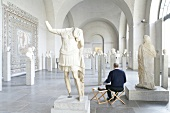 Man sitting in front of sculptures in Glyptothek Museum, Munich, Germany