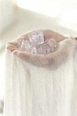 Hände halten Eiswürfel in einem Tuch