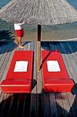Red sun loungers and beach umbrella at Hotel Casadelmar, Porto Vecchio, Corsica, France