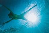 Unterwasser-Foto: brünette Frau im Bikini in Gelb beim Schwimmen, blau