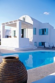 Holiday house with blue shutters beside pool, Greece