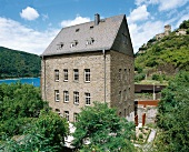 Dreistöckiges Steinhaus mit spitzem Dach am Reihnufer, Turm, viel Grün