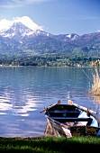 View of mountains overlooking boat moored near shore of Lake Worth, Austria