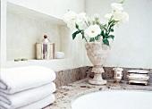 Ein Strauß Blumen in eleganter Vase auf Badewannenrand