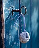 Schlüssel mit Stein als Anhänger im Schloss einer blauen Vintage Tür