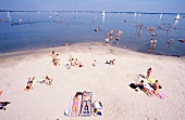 Tourists sunbathing on lakeshore of Steinhuder Meer, Steinhude, Germany