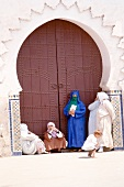 Women and children standing at gate of Koutubia mosque at Jemaa El Fna, Marrakesh, Morocco