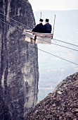 Two priests travelling in cable car over Gorge and Pelion mountains, Greece