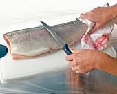 Schwanzende festhalten, mit einem Messer Schuppen abkratzen, Step 2