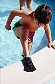 Little boy wearing flippers stepping out of swimming pool