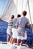 Rear view of three men wearing striped pattern sports outfit standing on sailboat