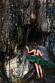Frau steht nackt und naß unter tropischem Wasserfall