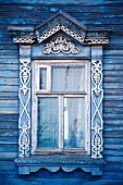 Close-up of typical decorated window on blue wooden house in Russia