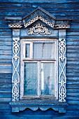 Typisches, verziertes Fenster an einem blauen Holzhaus in Russland