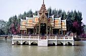 Thailändischer Tempel mit verzierten Dächern auf Pfählen im Fluss