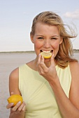 Jennifer Frau beisst in Zitronen- scheibe und lacht dabei