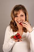 Charlotte Frau mit langen Haaren beisst in eine Erdbeere