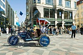 Commuter sitting in pedicab at Amager Square in Copenhagen, Denmark