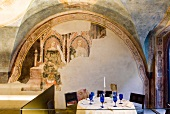 Medieval fresco and table with blue wine glass in Alle Murate restaurant, Firenze, Italy