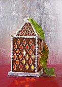 A lantern shaped like a gingerbread house, illuminated from within