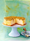 Passion fruit cheesecake on a cake stand, sliced
