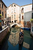 Tourists enjoying gondola ride in narrow canal with buildings on side, Venice, Italy