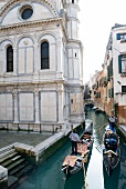 Facade of Santa Maria dei Miracoli church and two gondolas in narrow canal, Venice, Italy