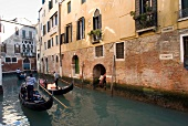 Tourists enjoying gondola ride in narrow canal, Venice, Italy