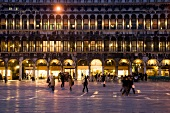 Buildings with illuminated arcades at Saint Mark's Square in evening, Venice, Italy