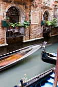 Gondolas speeding in narrow canal beside balcony, Venice, Italy, blurred motion