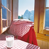 Glass of milk on red and white checked tablecloth and open window, Switzerland