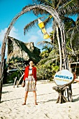 Pretty woman wearing jacket and colourful stripe dress holding coconut on beach