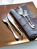 Silver cutlery and a blue napkin on a golden plate