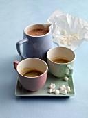 Espresso, chococcino with meringue sprinkles, cups and a jug