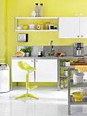 weiße Edelstahlküche vor gelber Wand , gelber Hocker, Espressomaschine