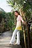 Contemplative woman wearing pink blouse and white pants leaning on bridge railings
