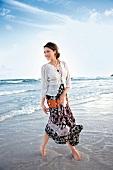 Frau, barfuß im Meer, langes Kleid, helle Strickjacke