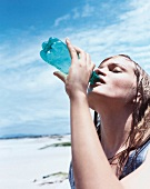 Frau mit nassem Haar trinkt Wasser aus einer grünen Flasche, Strand
