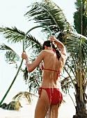 Rückansicht: Frau im roten Bikini du scht sich mit Wasserschlauch ab